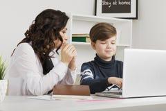 Madre ed suo figlio che fanno compito nella stanza bianca Compito di battitura a macchina su un computer portatile fotografie stock