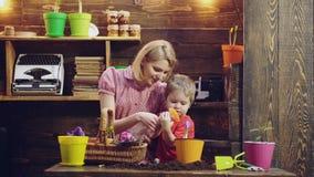 Madre ed suo figlio impegnati nel giardinaggio nel cortile Concetto, natura e cura della primavera Il ragazzo sveglio del bambino stock footage