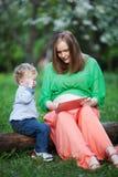 Madre embarazada con el pequeño hijo que usa la almohadilla táctil adentro Imagenes de archivo