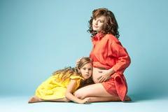 Madre embarazada con la hija adolescente Retrato del estudio de la familia sobre fondo azul Imagen de archivo libre de regalías