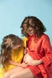 Madre embarazada con la hija adolescente Retrato del estudio de la familia sobre fondo azul Imágenes de archivo libres de regalías