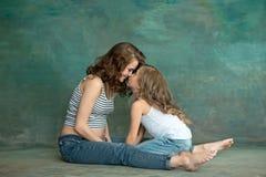 Madre embarazada con la hija adolescente Retrato del estudio de la familia sobre fondo azul Fotos de archivo