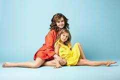 Madre embarazada con la hija adolescente Retrato del estudio de la familia sobre fondo azul Imagen de archivo