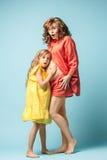Madre embarazada con la hija adolescente Retrato del estudio de la familia sobre fondo azul Foto de archivo
