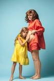 Madre embarazada con la hija adolescente Retrato del estudio de la familia sobre fondo azul Foto de archivo libre de regalías