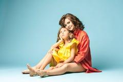 Madre embarazada con la hija adolescente Retrato del estudio de la familia sobre fondo azul Imagenes de archivo