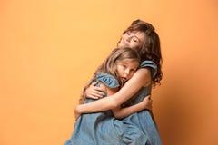 Madre embarazada con la hija adolescente Retrato del estudio de la familia sobre fondo marrón Imágenes de archivo libres de regalías