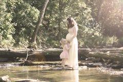 Madre embarazada con la hija por The Creek Foto de archivo