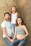 Madre embarazada con la hija y el marido adolescentes Retrato del estudio de la familia sobre fondo marrón Imagen de archivo