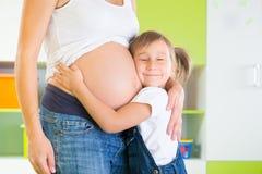 Madre embarazada de abarcamiento de la niña Imagen de archivo libre de regalías