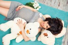 Madre embarazada hermosa con los osos de peluche Imágenes de archivo libres de regalías