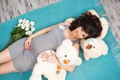 Madre embarazada hermosa con los osos de peluche maternidad Fotos de archivo