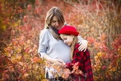 Madre embarazada joven feliz con la hija en parque del otoño Fotos de archivo libres de regalías