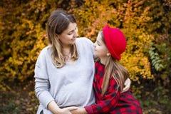 Madre embarazada joven feliz con la hija en parque del otoño Imágenes de archivo libres de regalías