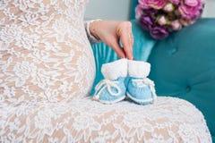 Madre embarazada que celebra poco zapatos de bebé de punto Foto de archivo
