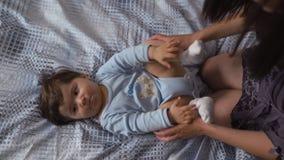 Madre embarazada que pone con su hijo del bebé en la cama del dormitorio que juega y que se divierte - muchacho mezclado asiático almacen de video