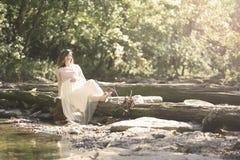 Madre embarazada que sienta en un inicio de sesión una cala Imagenes de archivo