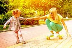 Madre emocional sonriente hermosa con su hija que monta a SK Fotos de archivo