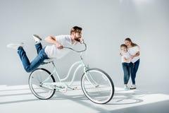 Madre emozionante e figlia che esaminano la bicicletta felice e divertiresi di guida dell'uomo fotografia stock