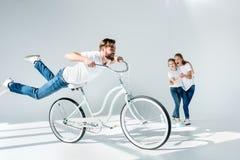 Madre emozionante e figlia che esaminano la bicicletta felice e divertiresi di guida dell'uomo immagini stock