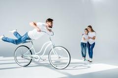 Madre emozionante e figlia che esaminano la bicicletta felice e divertiresi di guida dell'uomo fotografia stock libera da diritti