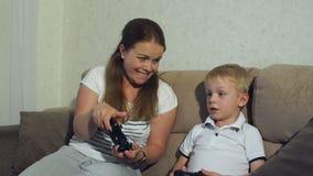 Madre emozionante e figlio che giocano insieme i video giochi a casa stock footage
