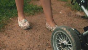 Madre en carro de bebé del rollo del vestido del verano y discurso en el teléfono en parque caminata almacen de video