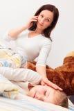 Madre en cuestión que habla en el teléfono Foto de archivo