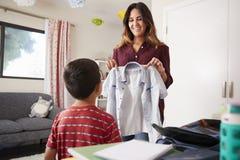 Madre en el hijo de ayuda del dormitorio para elegir la camisa para la escuela fotos de archivo libres de regalías