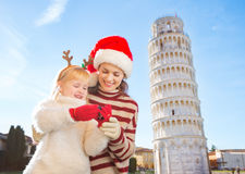Madre en el sombrero y la hija de la Navidad que comprueban las fotos pisa Fotografía de archivo