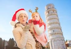 Madre en el sombrero y la hija de la Navidad que dan beso del aire en Pisa Fotos de archivo