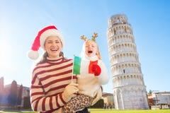 Madre en el sombrero y la hija de la Navidad que sostienen la bandera italiana pisa Imagen de archivo