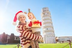 Madre en el sombrero y la hija de la Navidad que sostienen la caja de regalo pisa Fotos de archivo