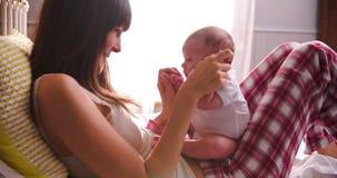 Madre en la cama que juega con la hija recién nacida del bebé almacen de video