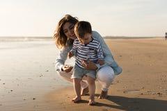 Madre en la playa con el niño Fotos de archivo libres de regalías