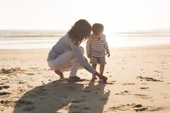 Madre en la playa con el niño Foto de archivo libre de regalías