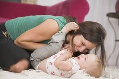 Madre en la sala de estar que juega con el bebé imagenes de archivo
