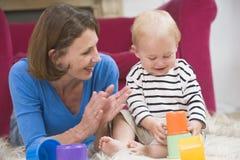 Madre en la sala de estar que juega con el bebé Imágenes de archivo libres de regalías