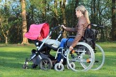 Madre en la silla de ruedas que empuja un cochecito de niño con el bebé Foto de archivo