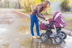 Madre en las sacudidas al aire libre un carro de bebé Fotos de archivo libres de regalías