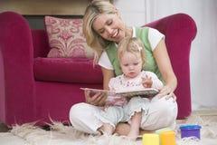 Madre en libro de lectura de la sala de estar con el bebé Imagen de archivo libre de regalías