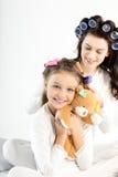 Madre en los bigudíes que encrespan el pelo a la pequeña hija feliz que abraza con el oso de peluche Imagenes de archivo
