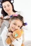 Madre en los bigudíes que encrespan el pelo a la pequeña hija feliz que abraza con el oso de peluche Fotografía de archivo