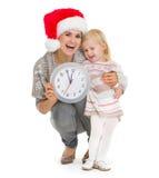 Madre en sombrero de la Navidad y reloj de la explotación agrícola del bebé Fotos de archivo