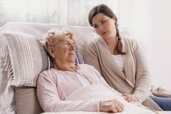 Madre enferma favorable joven que miente en cama de hospital fotografía de archivo