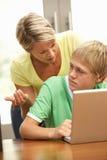 Madre enojada e hijo adolescente que usa la computadora portátil en el país Imagen de archivo libre de regalías