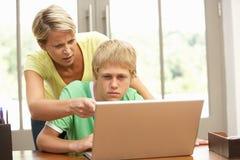 Madre enojada e hijo adolescente que usa la computadora portátil en el país Fotos de archivo