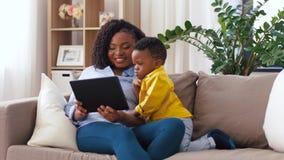 Madre facendo uso del pc della compressa con il figlio del bambino a casa archivi video