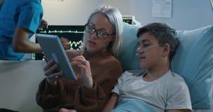 Madre facendo uso della compressa con il figlio malato archivi video