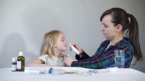Madre facendo uso dello spruzzo di naso per curare sua figlia video d archivio